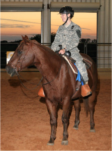 A military veteran participating in a therapeutic riding session.